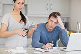 Disappointed couple in the kitchen cutting credit card