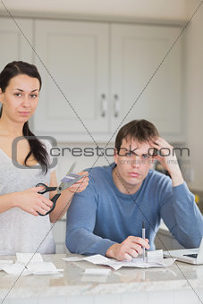 Woman cutting up credit card with man calculating finances