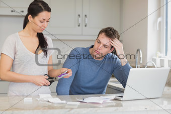 Wife cutting up credit card with husband watching