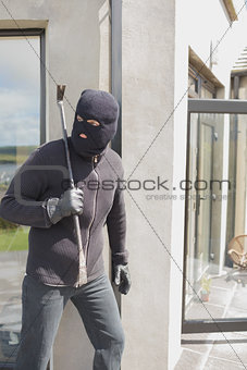 Burglar hiding behind wall