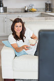 Woman watching television and smiling