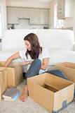 Woman happily unpacking moving boxes