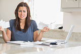 Woman looking troubled while holding bills