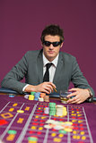 Man wearing sun glasses at roulette table