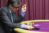 Man with gun sitting at poker table