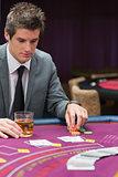 Man looking down at poker table