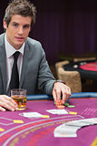 Man sitting at poker table with whiskey