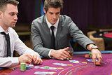 Men placing bets at poker game