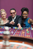 Man wearing sun glasses with women at roulette