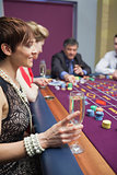 Woman holding glass of champagne at roulette