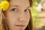 portrait of young teenager girl in park with dandelion in hair