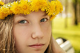 portrait of young teenager girl on bench with wreath of dandelions