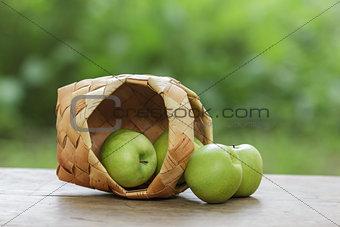 green apples in a birchbark basket