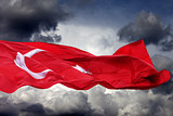 Waving flag of Turkey against storm clouds