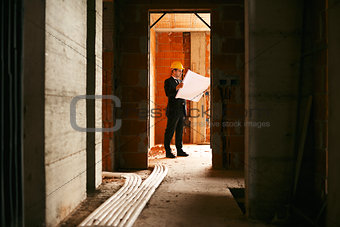 Architect standing in house under construction with building pla