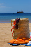 sunbathing accessories in straw bag