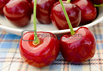 Two Ripe Sweet Cherries with the Full Plate on the Background