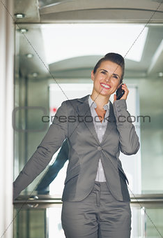 Smiling business woman talking mobile phone in elevator