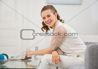 Portrait of smiling young housewife sitting on couch in living r