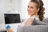 Smiling young housewife with laptop and credit card sitting on c