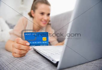 Closeup on credit card in hand of young woman laying on couch