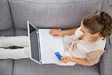 Young woman laying on sofa with laptop and credit card