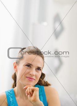 Portrait of thoughtful young woman in living room