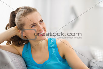 Portrait of happy young woman in living room looking on copy spa