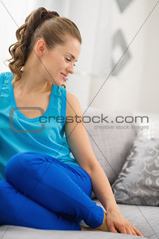 Happy young woman sitting on sofa in living room