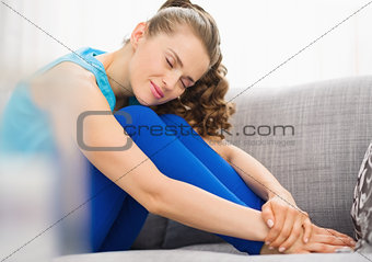 Happy young woman sitting on couch in living room