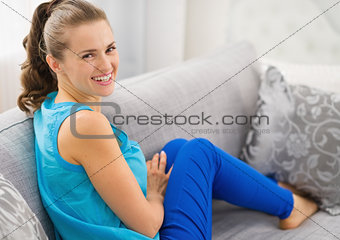 Smiling young woman sitting on divan in living room