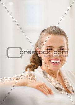 Portrait of happy young housewife in living room