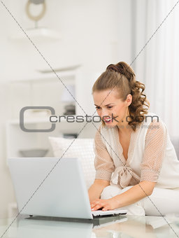 Happy young housewife sitting on divan and using laptop