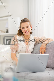 Smiling young woman sitting on sofa in living room with laptop