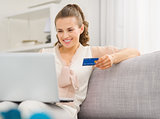 Happy young housewife with laptop and credit card in living room