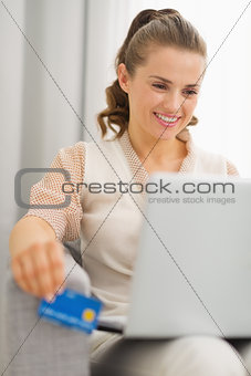 Smiling young housewife with laptop and credit card