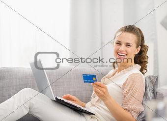 Happy young housewife laying on sofa with laptop and credit card