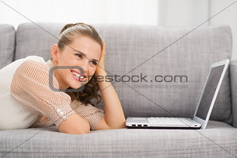 Thoughtful young woman laying on sofa with laptop