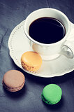 Cup of black coffee with macaroons