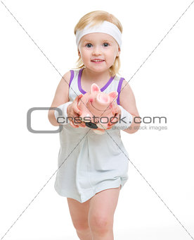 Baby in tennis clothes holding piggy bank