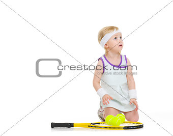 Baby in tennis clothes with racket and balls looking on copy spa