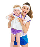 Portrait of smiling mother and baby in tennis clothes