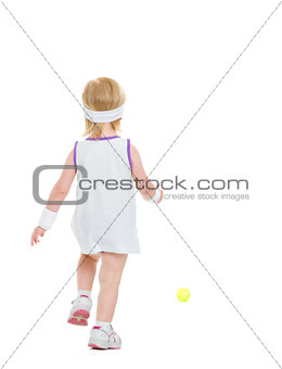 Baby running for tennis ball . rear view