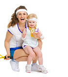 Portrait of mother and baby in tennis clothes holding medal