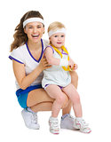 Portrait of mother and baby in tennis clothes with medal