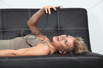 Woman on a couch at home listening to the music from a smartphone