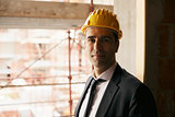 Engineer with helmet in construction site smiling at camera, por