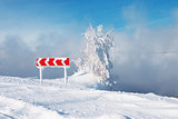 Frozen and snowed guide road sign of turn and tree in a blue foggy background