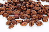 brown coffee beans scattered and isolated on a white background