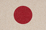Japanese flag made of colored decorative sand.